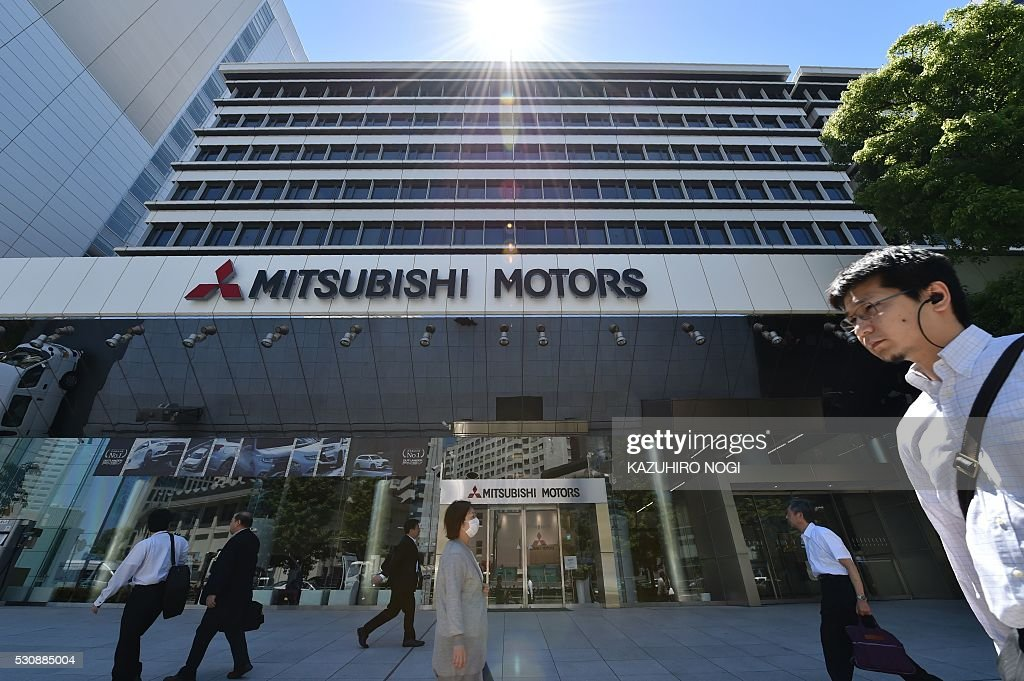 Pedestrians walk past the Mitsubishi Motors headquarters in Tokyo on May 12 2016 Nissan Motor confirmed May 12 2016 that it was in capital tieup...