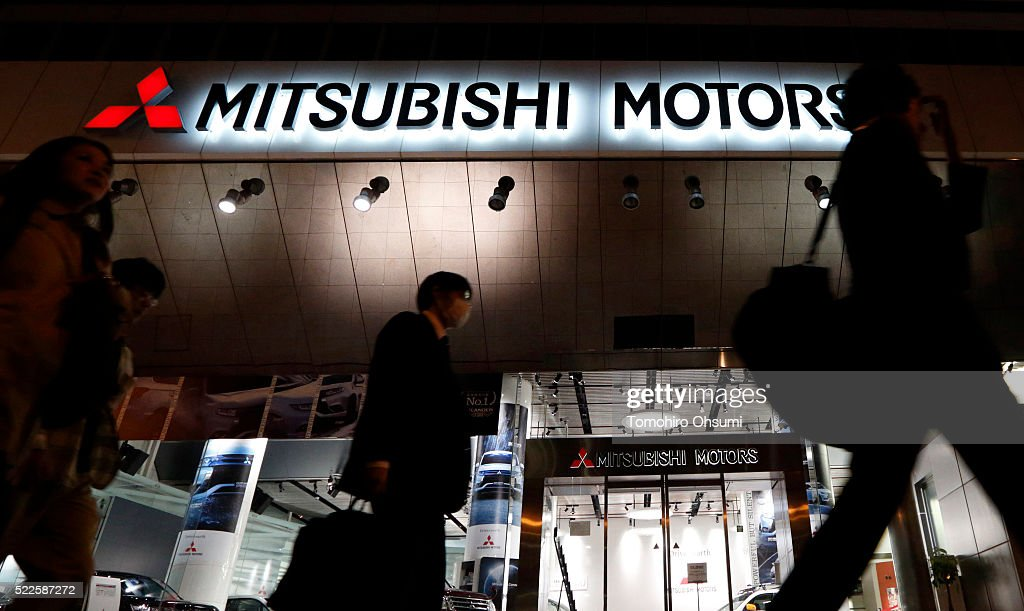 Pedestrians walk past the Mitsubishi Motors headquarters on April 20 2016 in Tokyo Japan Mitsubishi Motors share plunged more than 15% after the...
