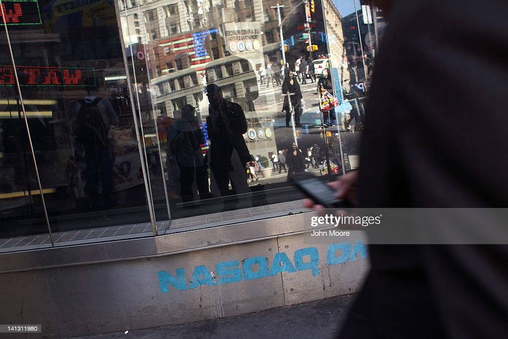 Pedestrians walk past the Nasdaq stock market at Times Square on March 14, 2012 in New York City. The tech-laden Nasdaq Composite Index surged over 3,000 this week, the first time it has reached that level since December 2000 at the end of the dot-com bubble.