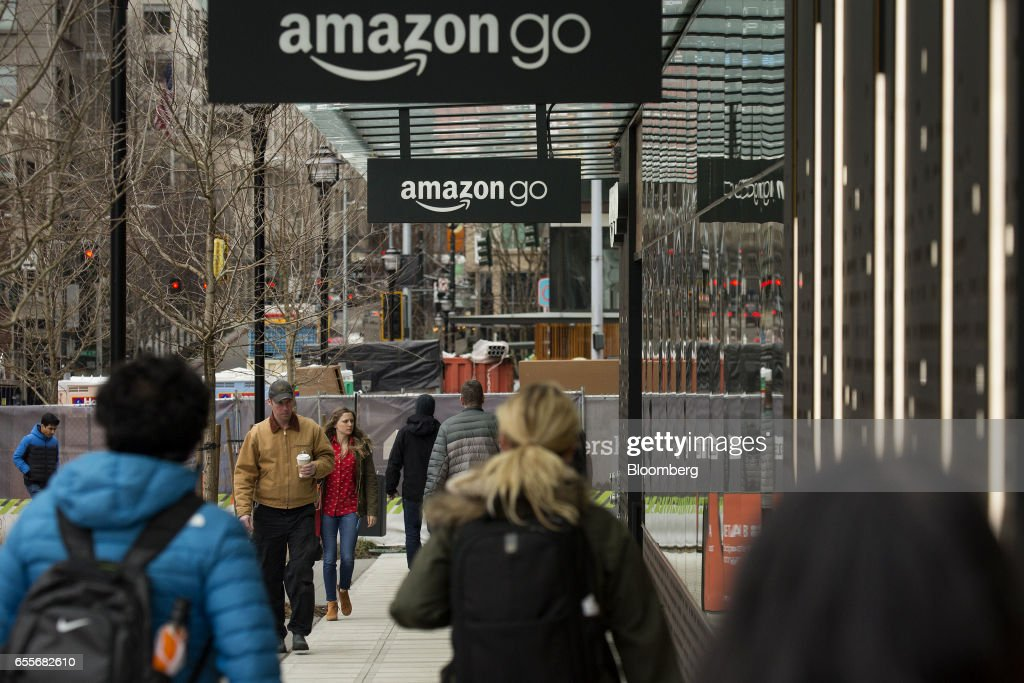 Pedestrians walk past the new Amazon.com Inc. Go grocery store in Seattle, Washington, U.S., on Wednesday, March 8, 2017. Amazon's goal is to become a Top 5 grocery retailer by 2025, according to a person familiar with the matter. That would require more than $30 billion in annual food and beverage spending through its sites, up from $8.7 billion including Amazon Fresh and all other food and drink sales in 2016, according to Cowen & Co. Photographer: David Ryder/Bloomberg via Getty Images