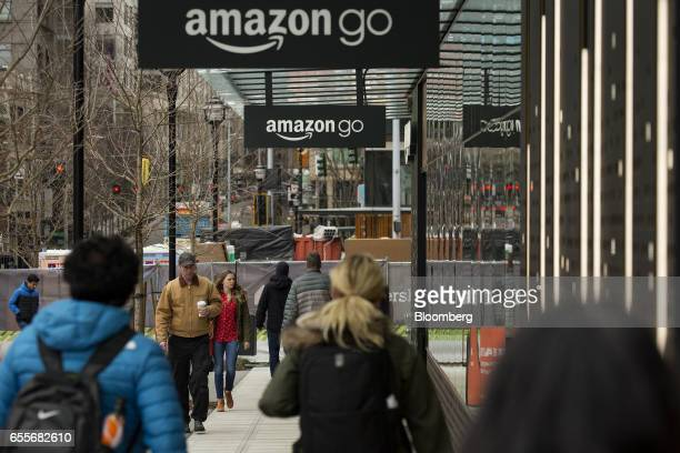 Pedestrians walk past the new Amazoncom Inc Go grocery store in Seattle Washington US on Wednesday March 8 2017 Amazon's goal is to become a Top 5...