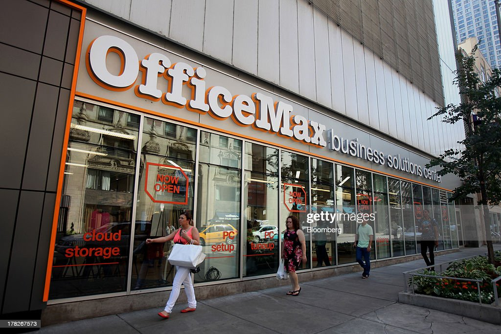 Pedestrians walk past the new OfficeMax Inc. Business Solutions Center in Chicago, Illinois, U.S., on Tuesday, Aug. 27, 2013. The OfficeMax Business Solutions Center provides local businesses with services including designed marketing, web, document, IT and shipping service. Photographer: Tim Boyle/Bloomberg via Getty Images