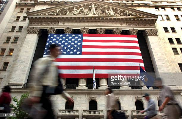 Pedestrians walk past the New York Stock Exchange July 16 2002 in New York City The Dow closed down in seven straight losing sessions falling more...