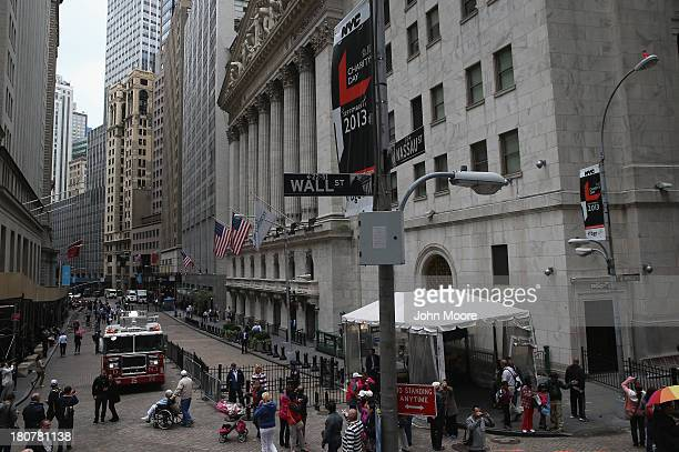 Pedestrians walk past the New York Stock Exchange on Wall Street on September 16 2013 in New York City Five years after the beginning of the...