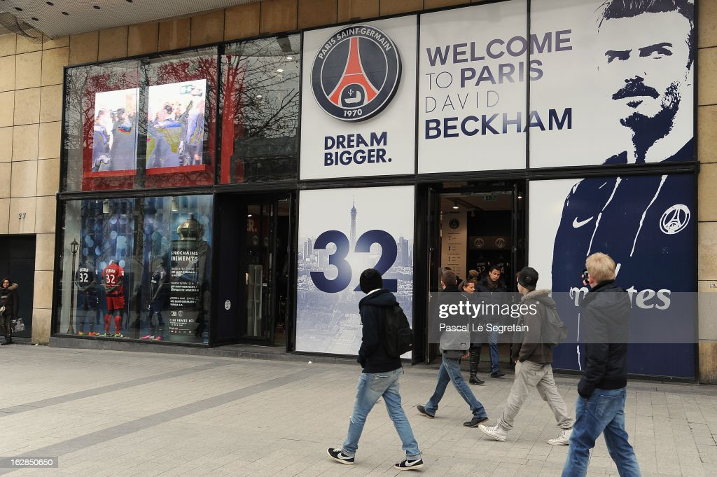 Pedestrians walk past the Paris Saint Germain football club's official shop displaying a portrait of David Beckham, that faces the adidas shop, prior to David Beckham attending an autograph session at adidas Performance Store Champs-Elysees on February 28, 2013 in Paris, France.
