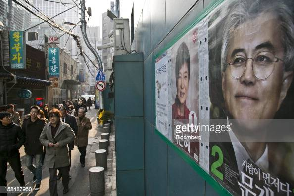 Pedestrians walk past the posters of South Korean presidential candidates Park Geun Hye from the ruling New Frontier Party left and Moon Jae In from...