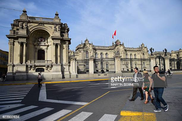 Pedestrians walk past the Presidential Palace in downtown Lima on November 17 2016 as the city hosts the AsiaPacific Economic Cooperation Summit Top...