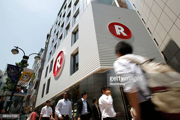 Pedestrians walk past the Rakuten Cafe operated by Rakuten Inc in Tokyo Japan on Thursday May 29 2014 Japan's retail sales dropped at the fastest...