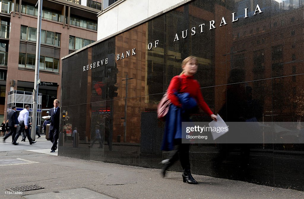 Pedestrians walk past the Reserve Bank of Australia (RBA) headquarters in the central business district of Sydney, Australia, on Monday, July 15, 2013. While the RBA previously needed higher interest rates to control price pressures as the Australian economy expanded since 1991 without a recession, Governor Glenn Stevens has slashed the cash target, predicting a mining boom will wane. Photographer: Dan Himbrechts/Bloomberg via Getty Images