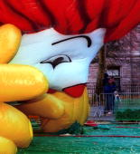 Pedestrians walk past the 'Ronald McDonald' float which is one of many being prepared for the Macy's Thanksgiving Day Parade November 22 2000 in New...