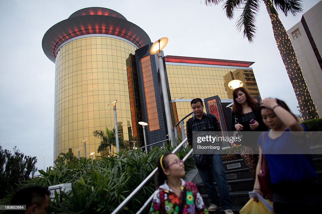 Pedestrians walk past the Sands Macao hotel and casino, operated by Sands China Ltd., a unit of Las Vegas Sands Corp., in Macau, China, on Wednesday, Feb. 6, 2013. Casino industry revenue in the gambling hub climbed 14 percent to a record 304 billion patacas ($38 billion) last year. Photographer: Lam Yik Fei/Bloomberg via Getty Images