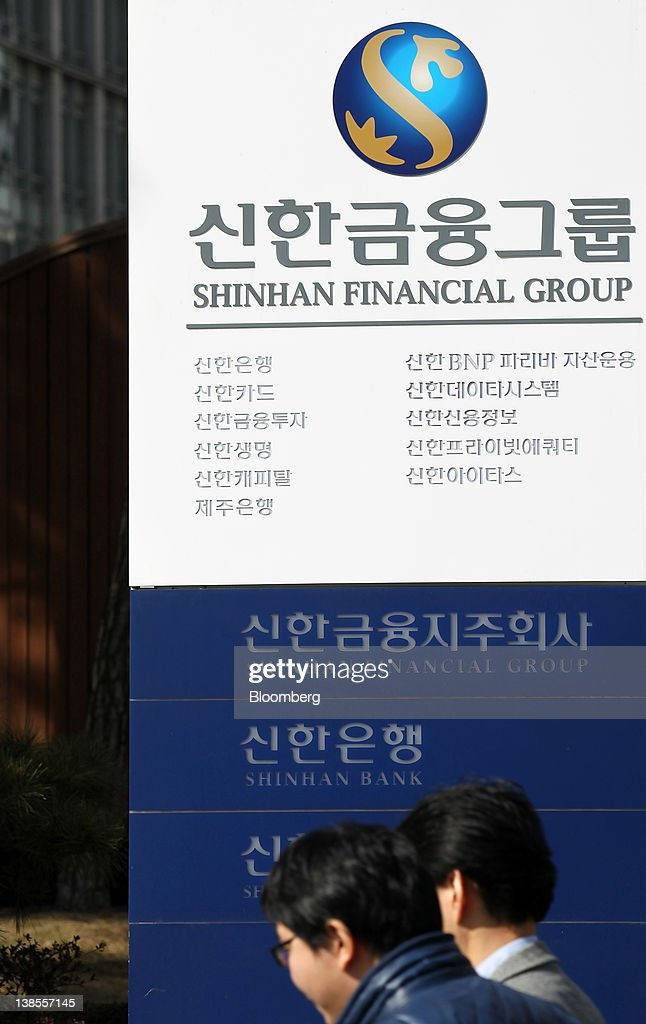 Pedestrians walk past the Shinhan Financial Group Inc. headquarters in Seoul, South Korea, on Thursday, Feb. 9, 2012. Shinhan Financial Group Inc., South Korea's largest financial services group by market value, said profit dropped 13 percent in the fourth quarter as the company set aside more provisions for bad debts. Photographer: SeongJoon Cho/Bloomberg via Getty Images