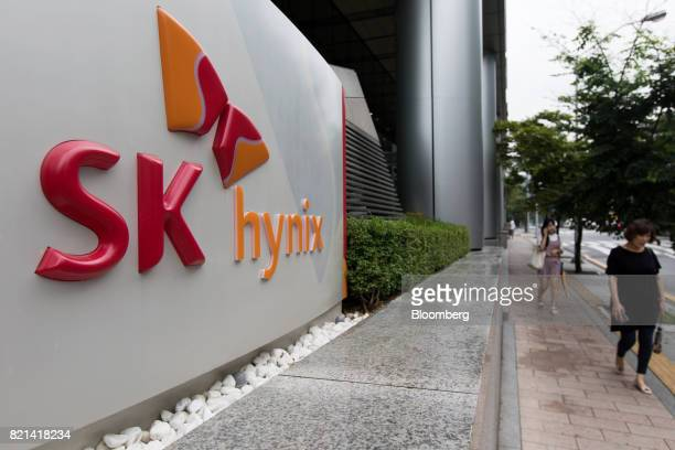 Pedestrians walk past the SK Hynix Inc logo displayed at the company's office building in Seongnam South Korea on Monday July 24 2017 SK Hynix is...