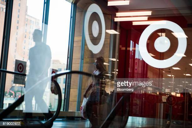 Pedestrians walk past the Target Corp logo reflected in a window at City Point in the Brooklyn borough of New York US on Tuesday July 18 2017...