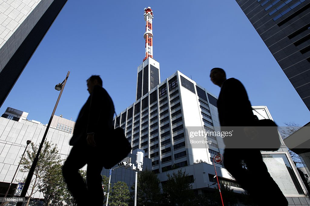 Pedestrians walk past the Tokyo Electric Power Co. (Tepco) headquarters, center, in Tokyo, Japan, on Wednesday, Nov. 7, 2012. Tepco may ask the government for more funds to cover decontamination and reactor decommissioning costs from last year's nuclear disaster at its Fukushima Dai-Ichi atomic plant. Photographer: Kiyoshi Ota/Bloomberg via Getty Images