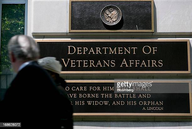 Pedestrians walk past the US Department of Veterans Affairs headquarters in Washington DC US on Friday May 10 2013 The department's funding has...