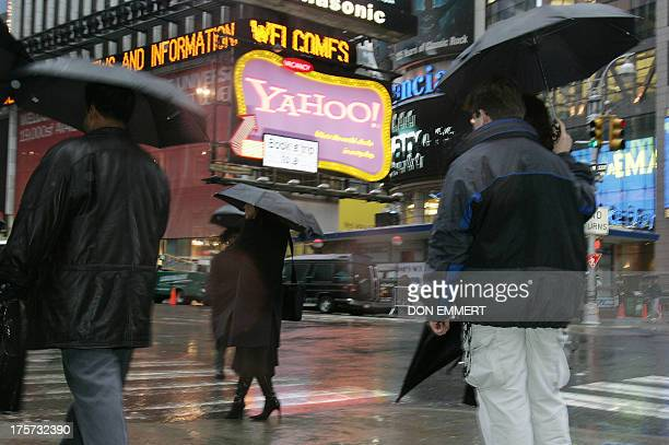 Pedestrians walk past the Yahoo sign in Times Square 18 January 2006 in New York Wall Street shares struggled again Wednesday after three losing...
