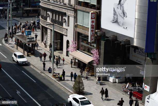 Pedestrians walk past the Yamano Music Co flagship store right in the Ginza district of Tokyo Japan on Monday March 20 2017 Japan's land prices will...