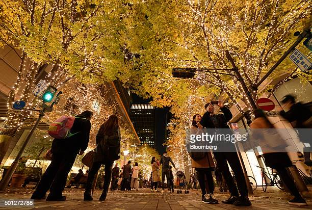 Pedestrians walk past trees decorated with illuminated Christmas lights at night in Tokyo Japan on Saturday December 5 2015 Confidence in Japan's...