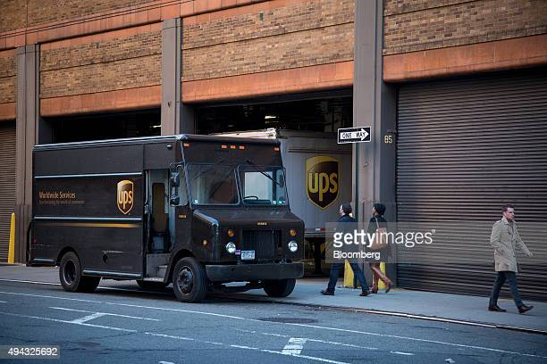 Pedestrians walk past trucks parked at a United Parcel Service Inc facility in New York US on Friday Oct 23 2015 UPS is scheduled to release...