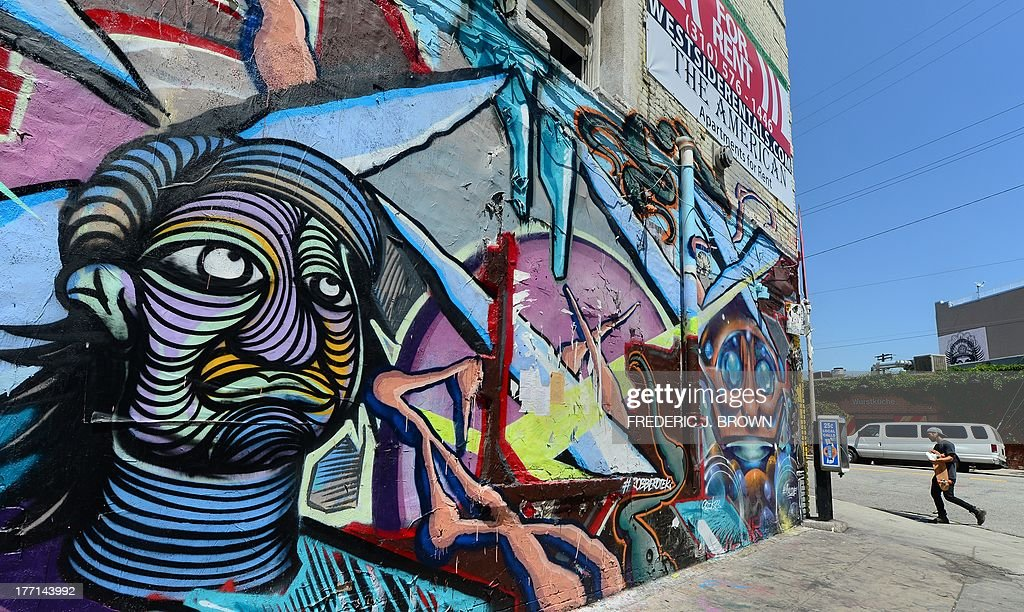 Pedestrians walk past vividly colourful murals on a building's exterior in the Arts Distrct near downtown Los Angeles on August 16, 2013 in California. AFP PHOTO/Frederic J. BROWN