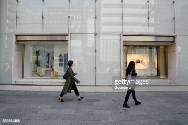 Pedestrians walk past window displays for Balenciaga SA left and Fendi SpA in the Ginza district of Tokyo Japan on Monday March 20 2017 Japan's land...
