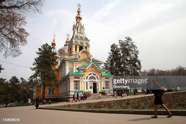Pedestrians walk past Zenkov cathedral in Panfilov Park in Almaty Kazakhstan on Monday April 9 2012 BTA Bank and Halyk Savings Bank welcome 'any...