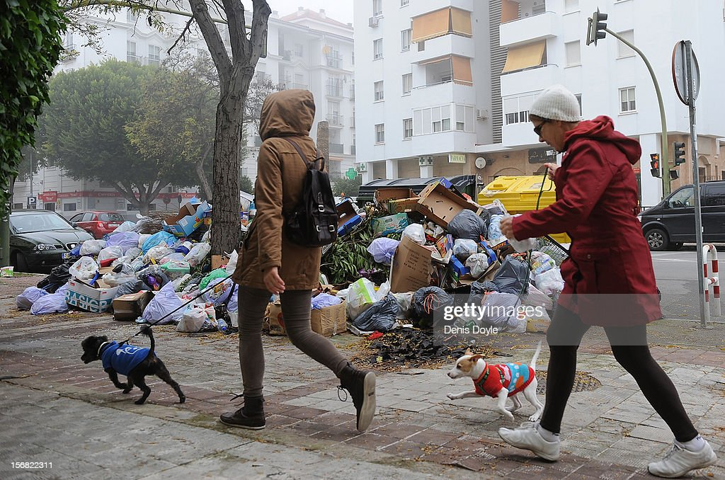 Pedestrians walk their dogs past a pile of uncollected garbage during the 21st day of the garbage collectors strike on November 22, 2012 in Jerez de la Frontera, Spain. The garbage collectors will vote today on a compromise deal which saves the 123 jobs due to be cut in favour of reductions in salaries.
