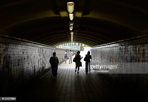 Pedestrians walk though an underground walkway towards the financial district in Singapore on July 11 2017 Singapore state investment giant Temasek...