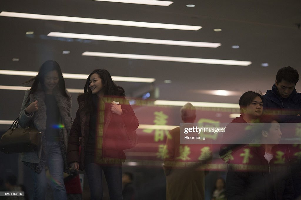 Pedestrians walk through a building in Hong Kong, China, on Friday, Jan. 4, 2013. Chief Executive Leung Chun-ying, who has been buffeted by student protests and low popularity since taking office on July 1, has pledged to tackle Asia's biggest wealth gap as the division between poor and rich widened to its worst level since at least 1971. Photographer: Jerome Favre/Bloomberg via Getty Images