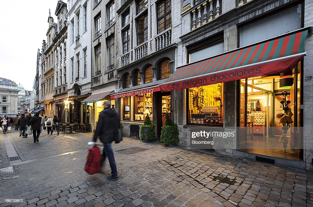 Pedestrians walk through a city centre street and past a store selling Belgian chocolates in Brussels, Belgium, on Monday, May 13, 2013. Euro-area data this week will probably reveal economic scars of the sovereign debt crisis confirming that the region is now suffering the longest recession since the single currency's creation. Photographer: Jock Fistick/Bloomberg via Getty Images