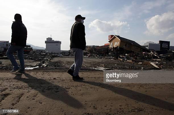 Pedestrians walk through a damaged street in Kesennuma City Miyagi Prefecture Japan on Friday April 1 2011 Japan begins forging a road map for...