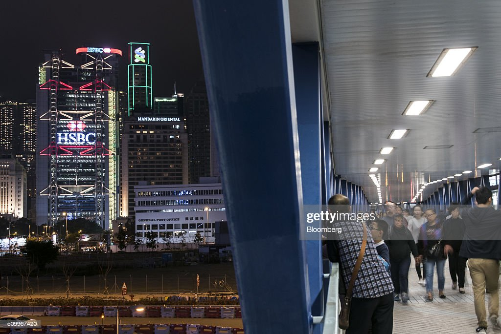 Pedestrians walk through a footbridge as the HSBC Holdings Plc logo is displayed on the company's headquarters building, left, at night in Hong Kong, China, on Saturday, Feb. 13, 2016. HSBC's board will meet on Sunday to decide whether to shift its headquarters from London, according to two people with knowledge of the decision. Photographer: Xaume Olleros/Bloomberg via Getty Images
