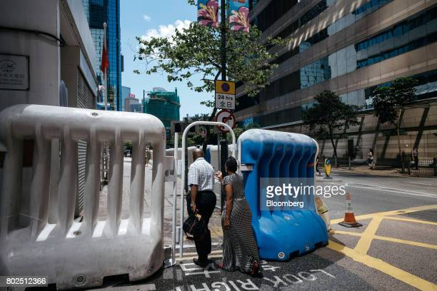 Pedestrians walk through a gate between water barricades near the Hong Kong Convention and Exhibition Center ahead of Chinese President Xi Jinping's...
