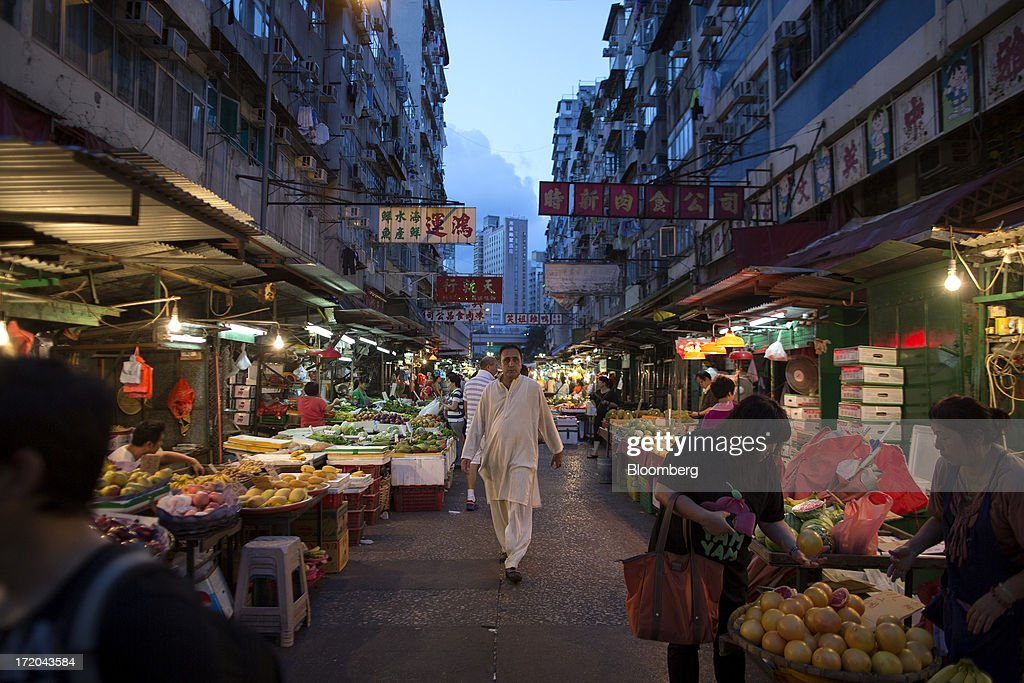 Pedestrians walk through a market in the Yau Ma Tei district of Hong Kong, China, on Saturday, June 29, 2013. Hong Kongs best-selling newspapers called on readers to join a march to mark the anniversary of the citys handover to China, saying the government has failed to address issues of poverty and universal suffrage. Photographer: Jerome Favre/Bloomberg via Getty Images