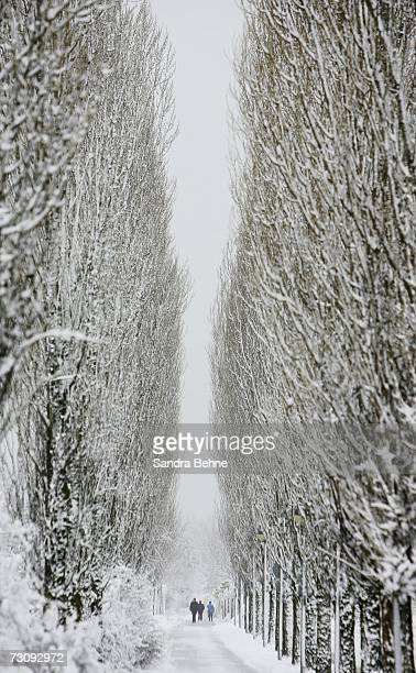 Pedestrians walk through a snow covered street on January 24 2007 in Unterhaching Germany After warmer temperatures than usual in the last decade...