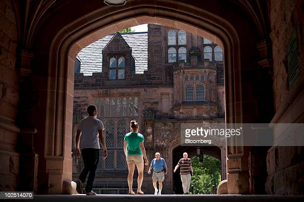 Pedestrians walk through arches of the East Pyne building on the Princeton University campus in Princeton New Jersey US on Monday June 21 2010...