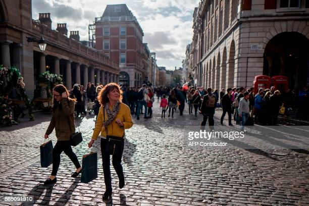 Pedestrians walk through Covent Garden in London on October 22 2017 Britain could be left 'poorer and weaker' by Brexit and needing to spend more to...