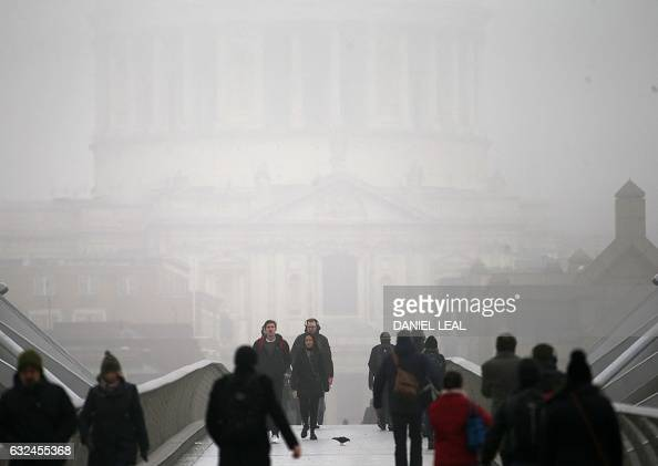 TOPSHOT Pedestrians walk through fog as they cross the Millennium Bridge backdropped by St Paul's Cathedral in London on January 23 2017 / AFP /...