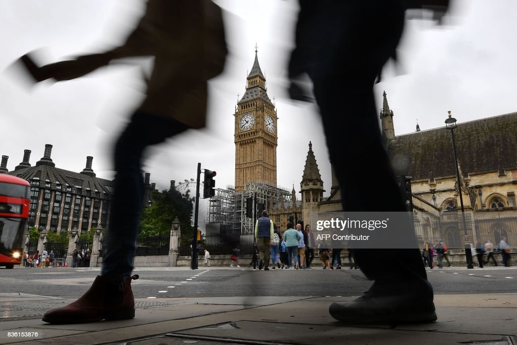 TOPSHOT - Pedestrians walk through Parliament Square at the Houses of Parliament in London on August 21, 2017 past Elizabeth Tower and Big Ben ahead of the final chimes of the famous bell before renovation works begin. Britain's Big Ben bell fell silent on August 21 for four years of renovation work, with its final 12 bongs ringing for midday in front of a crowd of over a thousand people. The repair work on the landmark looming over the Houses of Parliament in Westminster has sparked protests including from Prime Minister Theresa May. STANSALL