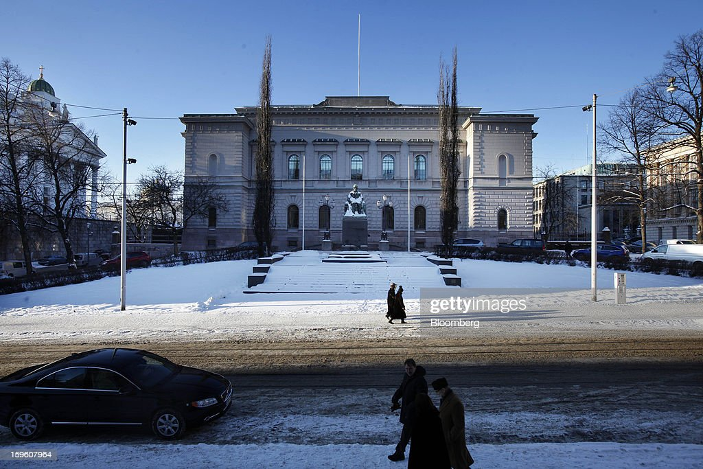 Pedestrians walk through snow outside the Finnish central bank in Helsinki, Finland, on Thursday, Jan. 17, 2013. The pace of Finland's debt growth is alarming and the country must undertake economic reforms together with reining in spending, Finnish Prime Minister Jyrki Katainen said in an op-ed piece published in newspaper Savon Sanomat. Photographer: Ville Mannikko/Bloomberg via Getty Images