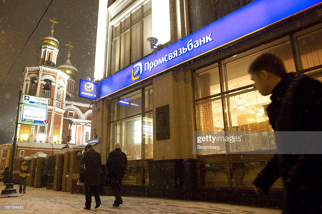 Pedestrians walk through snow past an illuminated branch of OAO Promsvyazbank near a Russian orthodox church in Moscow, Russia, on Wednesday, Nov. 28, 2012. Bank Rossii proposes government create rule limiting increases of budget funds held at central bank, RIA Novosti reports, citing First Deputy Chairman Alexey Ulyukayev. Photographer: Andrey Rudakov/Bloomberg via Getty Images