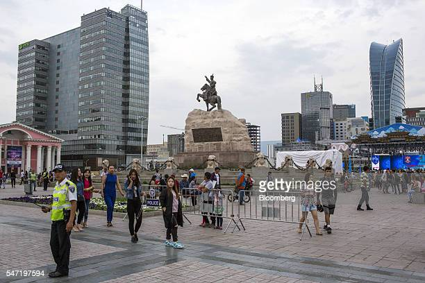 Pedestrians walk through Sukhbataar Square known as Chinggis Square in Ulaanbaatar Mongolia on Wednesday July 13 2016 The nation's growth slowed to...