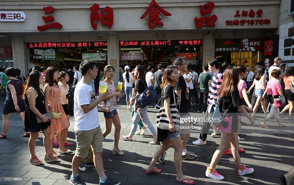 Pedestrians walk through the East Nanjing Road area in Shanghai, China, on Sunday, June 30, 2013. China's President Xi Jinping said officials shouldn't be judged solely on their record in boosting gross domestic product, the latest signal that policy makers are prepared to tolerate slower economic expansion. Photographer: Tomohiro Ohsumi/Bloomberg via Getty Images