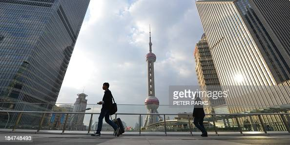 WITH 'CHINAUSDEBTFOCUS' BY Pedestrians walk through the financial district of Shanghai on October 16 2013 A US debt default could spur China to...