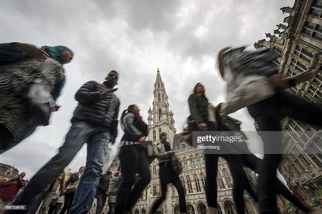 Pedestrians walk through the Grand Place and past Brussels City Hall in Brussels, Belgium, on Monday, May 13, 2013. Euro-area data this week will probably reveal economic scars of the sovereign debt crisis confirming that the region is now suffering the longest recession since the single currency's creation. Photographer: Jock Fistick/Bloomberg via Getty Images