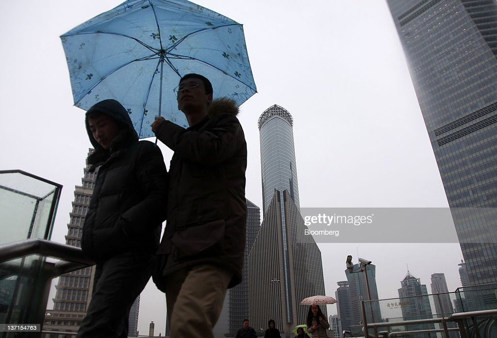 Pedestrians walk through the Lujiazui Financial District in Shanghai, China, on Sunday, Jan. 15, 2012. China's economy probably grew the least in 10 quarters in the last three months of 2011 and may cool further as export demand slumps and officials prolong a campaign against property bubbles. Photographer: Qilai Shen/Bloomberg via Getty Images