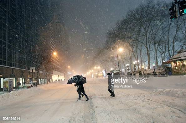 Pedestrians walk through the snowy streets near Bryant Park as all cars but emergency vehicles are banned from driving on the road on January 23 2016...
