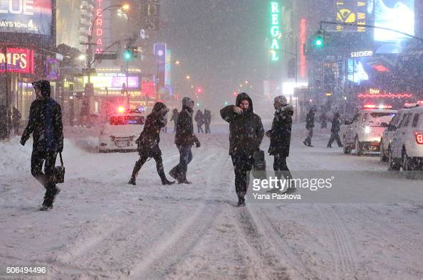 Pedestrians walk through the snowy streets near Times Square as all cars but emergency vehicles are banned from driving on the road on January 23...