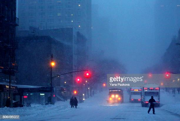 Pedestrians walk through the snowy streets of the Upper East Side as all cars but emergency vehicles are banned from driving on the road on January...
